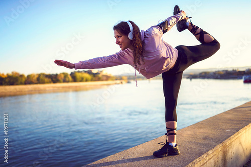 Young woman jogger resting listening music by the river