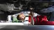 Automechaniker repariert Fahrzeug in einer Werkstatt in Arbeitskleidung am Unterboden - Closeup // Car mechanic repairs vehicle in a workshop in work clothes on the underbody
