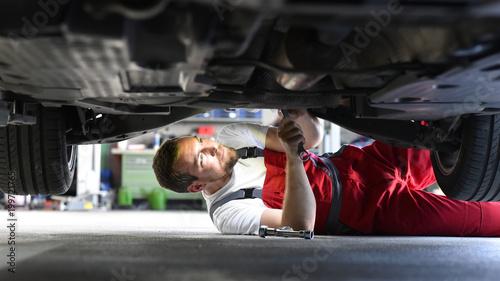 Samochód mechanik naprawia pojazd w warsztacie w odzieży roboczej na podwoziu - Zbliżenie // Samochód mechanik naprawia pojazd w warsztacie na podwoziu