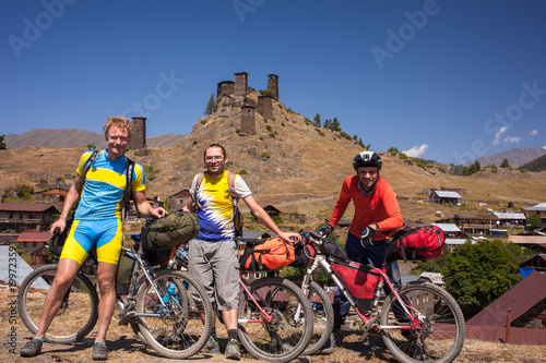 Mountain bikers are posing to the camera in front of Omalo towers, Tusheti region, Georgia