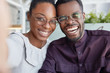 Positive dark skinned smiling woman and man have fun together, make selfie, wear glasses, laugh, happy to meet, being good friends, have good friendly relationships. Pleased African American couple