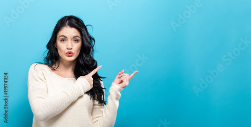 Young woman with a displaying hand gesture a solid background
