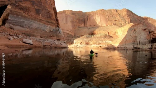 Kayaking through clear smooth water. Red sandstone cliffs rise from the lake as the kayak paddles away into the sunlight. © Shandra