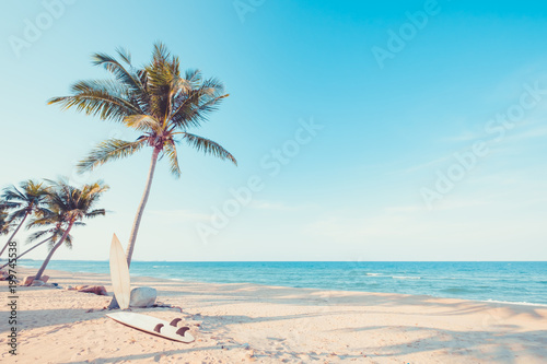 Vintage surf board with palm tree on tropical beach in summer. vintage color tone - 199745538