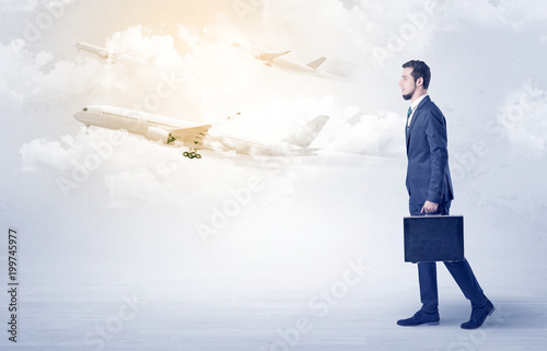 Foto Murales Elegant businessman going somewhere with briefcase and airplane on the background