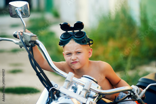 baby boy playing on his father's motorcycle . Dream to become a biker