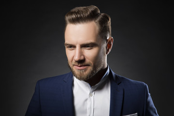 Handsome smiling man portrait. Beard, hairstyle, blue suit and white shirt. Dark studio background