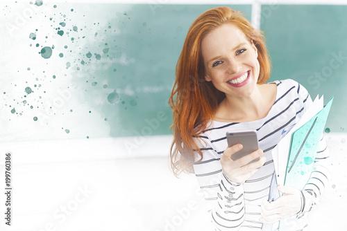 Młoda rozochocona kobieta z telefonem komórkowym w klasie