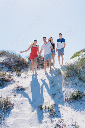 Two young couples walking across sand dunes