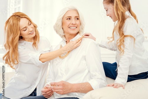 This style suits you very well. Cheerful ladies wearing matching attire sitting on a sofa and grinning broadly while playing with jewelry and enjoying family time spent together.