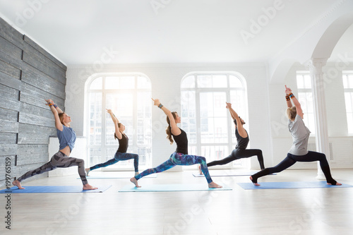Fototapeta Group of people doing yoga warrior pose at white studio with gesture of will. Fitness class, sport and healthy lifestyle concept