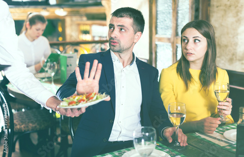 Man is refusing salad in time dining with woman - 199766371