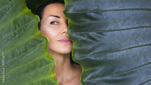 Beautiful Woman face with Natural nude make-up on a tropical leaf background. Healthy life. Purity