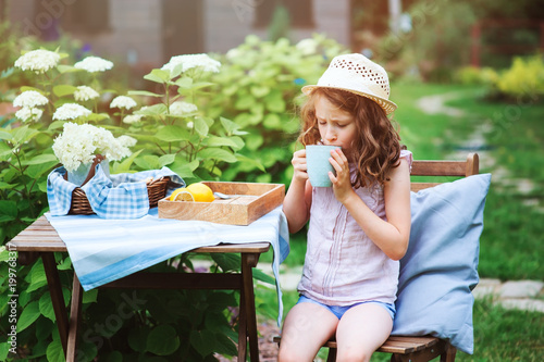 Wall mural happy child girl drinking tea with lemons in summer garden in the morning.