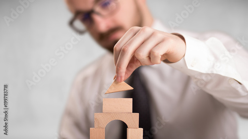 Foto Murales Young handsome businessman using wooden building blocks