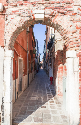 Poster Smal steegje access to a narrow alley by a brick arched doorway. Venice, Italy