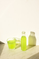 Green lemonade on a marble surface, glass, clear the glass and bottles under natural sunlight