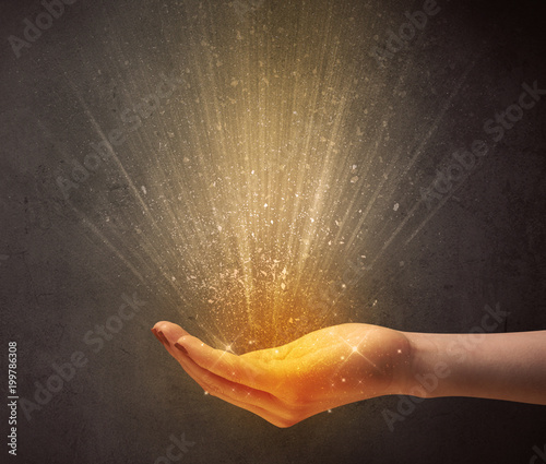 Foto Murales Yellow ray of light coming from a young hand