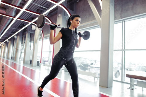 Aluminium Fitness Fit girl doing lunges with barbell in modern gym