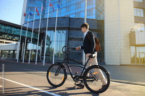Confident young businessman walking with bicycle on the street in town.