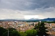 View of the city of Girona from the medieval pedestrian border wall. Roofs of houses, trees. Storm clouds over the city, somewhere sunlight makes its way through the clouds. Girona, Spain - 199806956