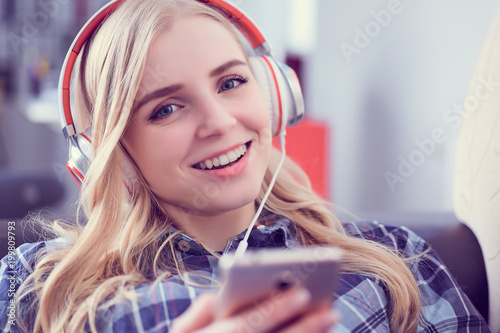 Fototapeta Happy smiling girl in casual clothes listening music and selecting songs on a smart phone lying in a couch at home.