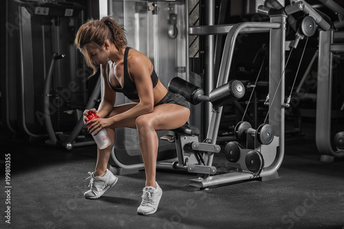Aluminium Fitness Young sporty woman listening to music on smartphone in gym. Break after hard workout.