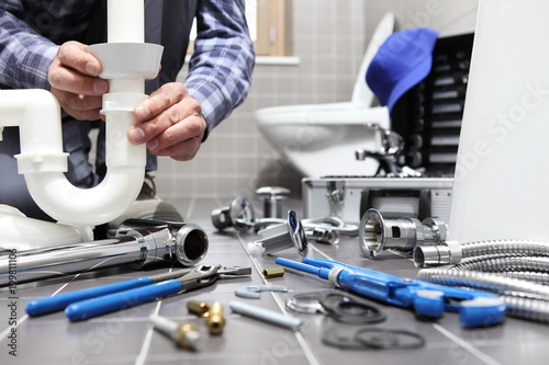 Leinwandbild Motiv plumber at work in a bathroom, plumbing repair service, assemble and install concept