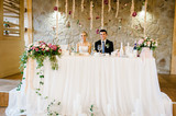 The bride and groom sit at the table and celebrate the wedding in the banquet hall of the restaurant. Newlyweds of the indoors. Wedding ceremony decorated with flowers and greenery.