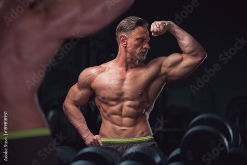 Poster Muscular sexy fitness model posing shirtless on the background of gym equipment. Mature man showing perfect relief body.
