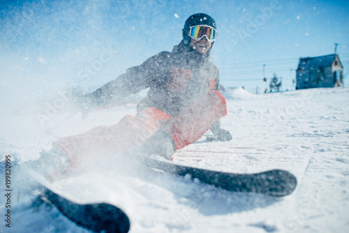 Skier lies on snowy surface of speed slope - 199820995