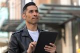 Hispanic man in city using tablet computer - 199825784