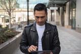 Hispanic man in city using tablet computer - 199825903