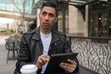 HIspanic man in city using tablet computer - 199826145