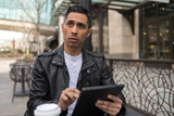 HIspanic man in city using tablet computer - 199826160