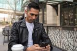 HIspanic man in city using cell phone - 199826183