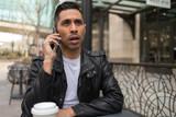 HIspanic man in city talking on cell phone - 199826315