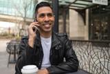 HIspanic man in city talking on cell phone - 199826333