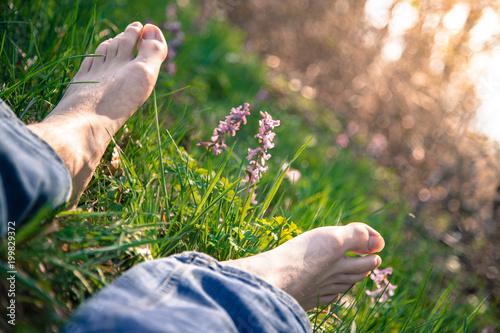 Männerbeine / Füße in Frühlingswiese, entspannt  - 199829372