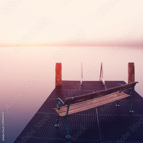 Plexiglas Pier Empty footbridge with a bench on a lake Altausseer at sunrise