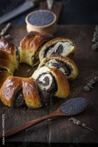 baked round pie with poppy seeds on a brown wooden cutting board