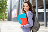 Portrait of a young student with backpack going to school and holding notebook - Back to school