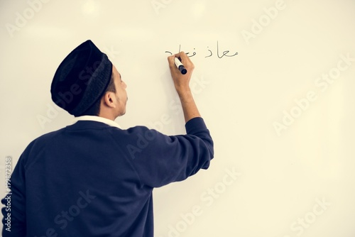 Foto op Plexiglas Dubai Young muslim man is writing a white board