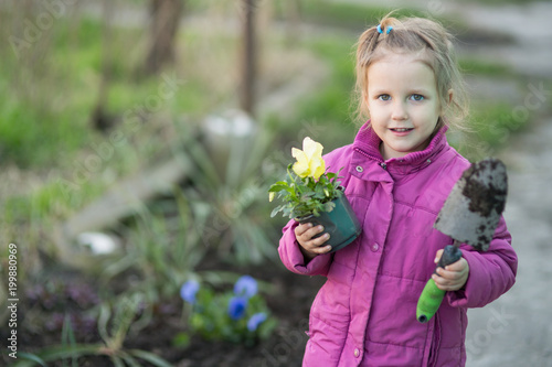 Wall mural  girl helps plant flowers