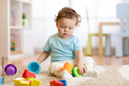 baby kid toddler playing toys at home or nursery