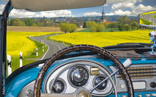view from inside a retro cabriolet riding a country road