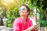 Beautiful mature woman with a cocktail of tropical fruits in her hands. Rest and travel on pension - 199892521