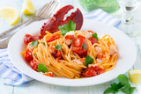 Spaghetti with lobster and cherry tomatoes served on white plate - 199893735