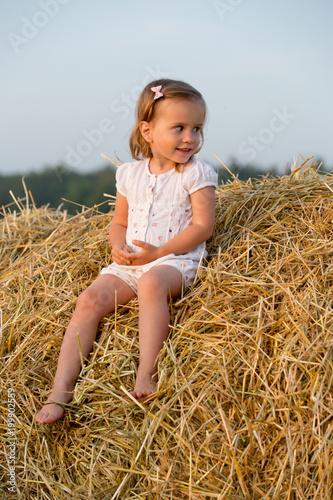 Little girl walking in the grain fields