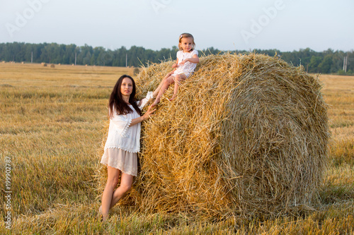 Mom and daughter walking in the grain fields